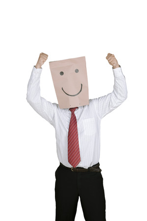 Happy businessman with a paper bag on his head, expressing his success while raising hands in the studio Stock Photo