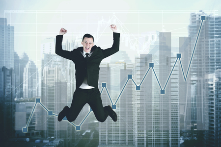 Picture of European businessman celebrating his success while jumping with growth statistic Foto de archivo