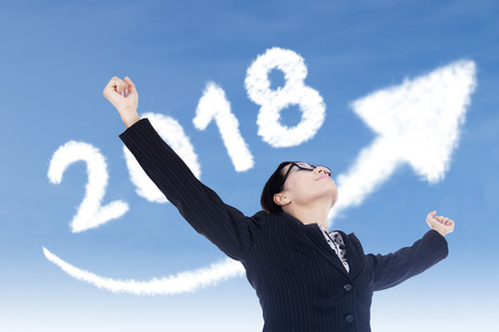 Image of beautiful businesswoman raising her hands with clouds shaped number 2018 and upward arrow in the sky Stock Photo
