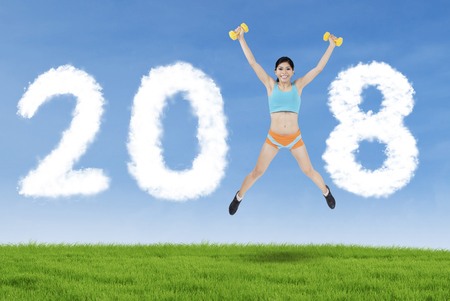 Sporty woman lifting two dumbbells while jumping in the meadow and forming numbers 2018 in the sky