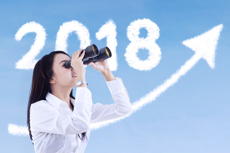 Young businesswoman using a binocular while looking at clouds shaped number 2018 and upward arrow in the sky