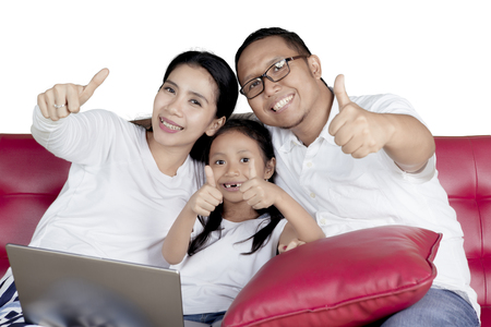 Cheerful family sitting on the sofa with a laptop computer and showing thumbs up, isolated on white background
