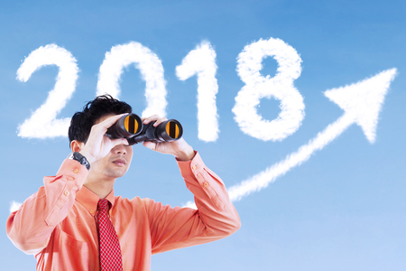 Young businessman using a binocular for looks at clouds shaped number 2018 and upward arrow in the sky