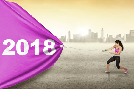 Young woman wearing sportswear while pulling numbers 2018 in a banner with city background Foto de archivo