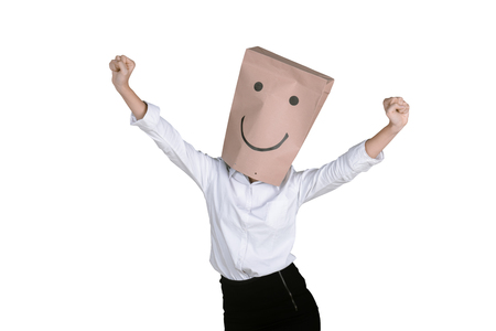 Portrait of happy unknown businesswoman expressing her success with a paper bag on her head Stock Photo