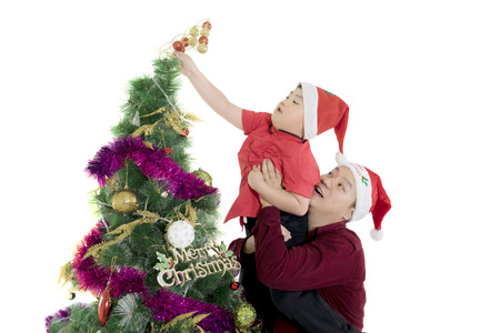 Young father helping his son to put a Christmas ornament on the pine tree, isolated on white background Standard-Bild