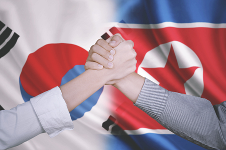 Closeup of two business partners shaking hands after deal business with flag of South Korea and North Korea in the background Stock Photo