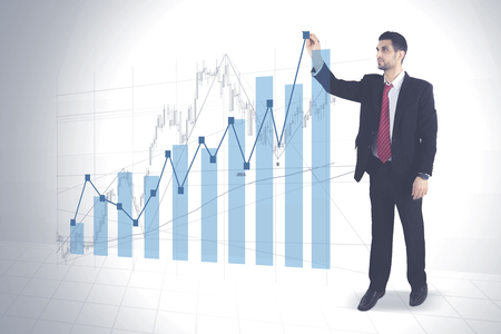 Portrait of Arabian businessman wearing a formal suit while drawing growth finance graph Stock Photo