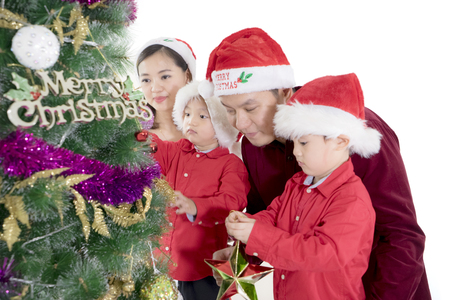Young parents helping their sons to decorate a Christmas tree in the studio, isolated on white background