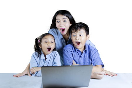 Photo of two elementary students with their teacher looks shocked while using a laptop computer, isolated on white background