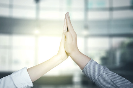 Hands of two business people giving high five together with sunlight background