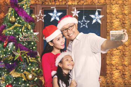 Cheerful parents with their daughter taking selfie photo together while standing near a Christmas tree at home Stock Photo