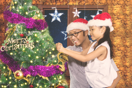 Image of young man decorating a fir tree with his daughter in the living room. Shot at Christmas time Stock Photo