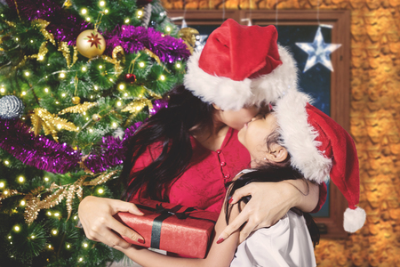 Picture of young mother kissed by her daughter while celebrating Christmas at home