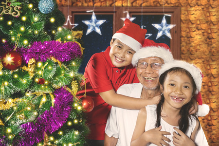 Image of two children playing with their grandfather near a Christmas tree at home