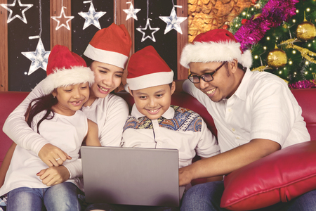 Portrait of happy family using a laptop computer while sitting on the couch. Shot at Christmas time