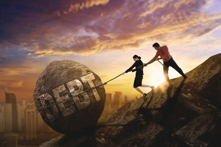 Two business team pulling word of debt in the stone while climbing on the cliff, Shot at sunset time