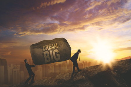 Picture of business people climbing on the cliff while carrying a stone with a text of dream big, Shot at sunset time Фото со стока - 91609974
