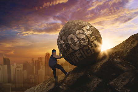 Fat man struggling to push a stone with text of lose weight while climbing on the cliff Stock Photo
