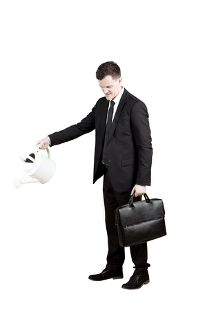 Portrait of a young male manager holding a suitcase while using a watering can in the studio Stock Photo