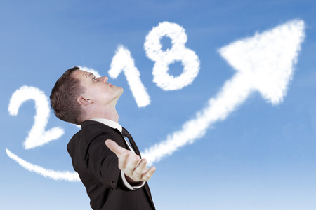 American businessman outstretched his hands with clouds shaped number 2018 and upward arrow in the sky
