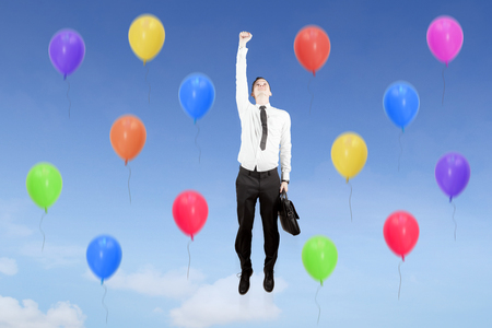 Image of European businessman carrying a suitcase while flying with colorful balloons in the blue sky