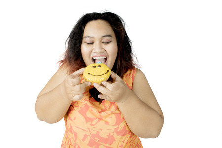 Image of overweight woman looks happy while eating a sweet doughnut, isolated white background