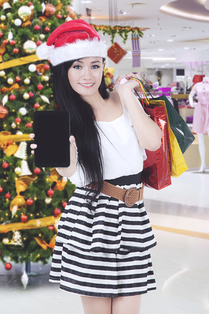 Asian woman showing a blank screen her smartphone after shopping Christmas gift in the mall Stock Photo
