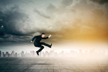Picture of young male manager looks hurry while running with skyscrapers in the background Stock Photo