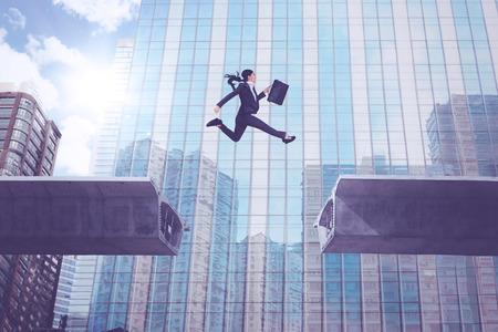 Junge Geschäftsfrau, die einen Koffer beim Springen über Brückenabstand mit einem Bürogebäudehintergrund trägt