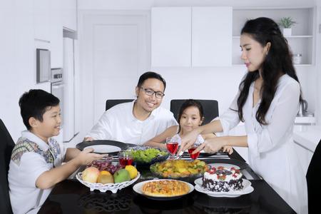 自宅で一緒に昼食を食べながら、夫と子供のためにローストチキンを提供するかわいい女性