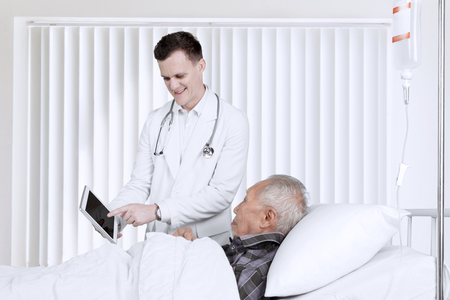 Friendly Caucasian doctor explaining the medical report with a digital tablet on elderly male patient. Shot in the inpatient room
