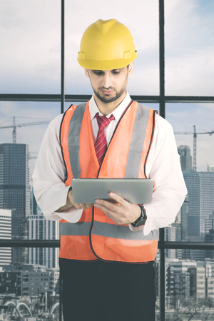 Italian foreman using a digital tablet while standing in the office with background construction sites Banque d'images