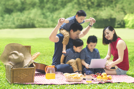 Image of Asian family using a laptop while enjoying holiday and picnicking in the park