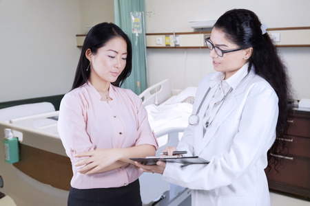 Female doctor holding a clipboard while explaining diagnosis to her patient in the hospital