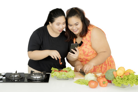 Image of two fat women looking at the smartphone while making healthy salad, isolated on white background Banque d'images