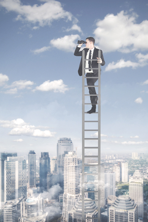 Portrait of young businessman standing on the ladder while using binoculars above modern city
