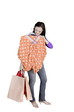 Portrait of young Caucasian woman holding a dress while carrying shopping bags, isolated on white background Stock Photo