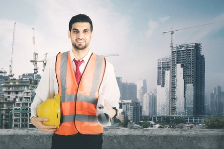 Portrait of male engineer smiling at the camera while standing on the rooftop. Shot at the construction site