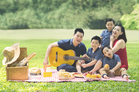 Image of Chinese family enjoying holiday while picnicking and playing a guitar together in the park