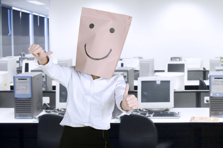 Unknown businesswoman with paper bag on her head while showing thumbs up in the workplace Stock Photo