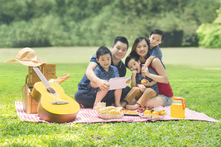 Young parents holding a digital tablet while enjoying holiday and picnicking with their sons in the park