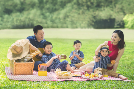 Picture of cute three children enjoying their holiday and picnicking with their parents in the park Stock Photo