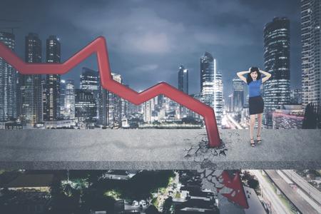 Asian businesswoman having headache while standing near downward arrow on the bridge Stock Photo