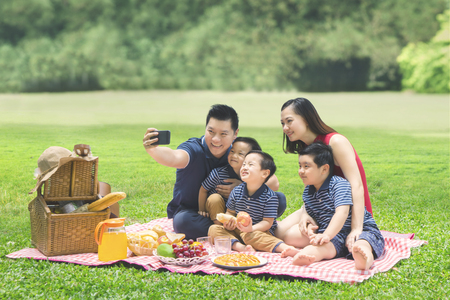 Asian family taking a picture by using a mobile phone while picnicking together in the park Foto de archivo