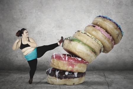 Portrait of overweight young woman wearing sportswear while kicking a pile of donuts Banque d'images
