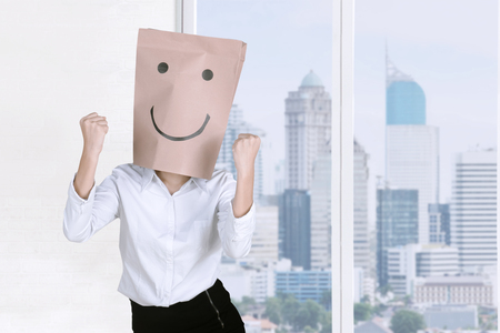 Female entrepreneur with paper bag on her head while expressing her success and standing near the window