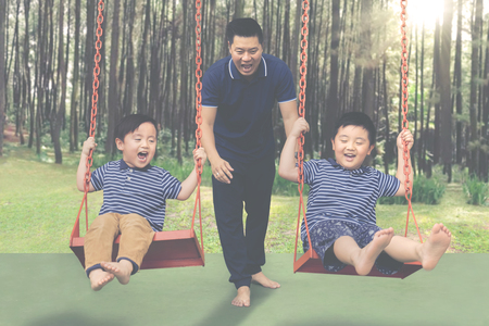 Image of two children sitting on the swing while having fun with their father in the park Banque d'images