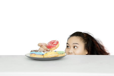 Picture of fat woman peeping near the table and stealing a doughnut on the plate, isolated on white background Banque d'images