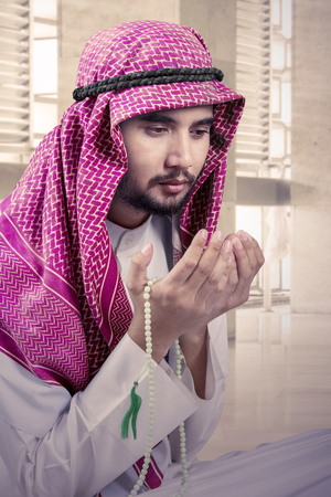 Arabic man wearing traditional clothes praying and holding beads while sitting in the mosque